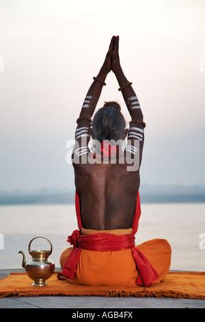 Sadhu o uomo santo eseguendo manas puja Fiume Gange Varanasi India Foto Stock