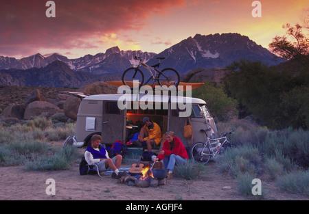Due uomini e una donna seduta intorno a un falò accanto ad un furgone con la mountain bike e un kayak e le montagne sullo sfondo