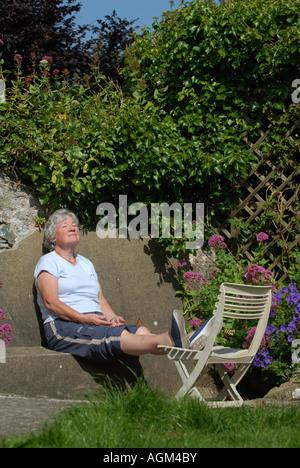 Un anziano pensionato donna gode di sole nel suo giardino murato.UK Foto Stock