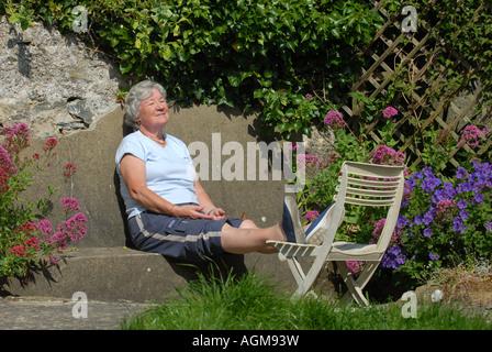 Una vecchiaia pensionato donna gode di sole nel suo giardino sul retro RE il pensionamento autunno anni.UK Foto Stock