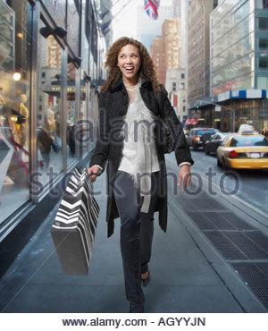 La donna il trasporto delle borse della spesa giù strada urbana Foto Stock