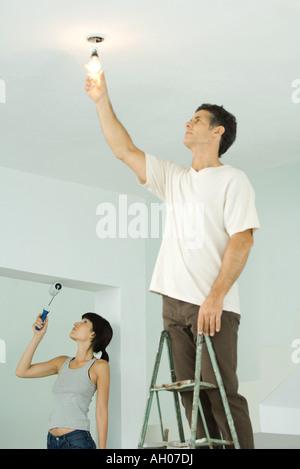 La donna la verniciatura con vernice a rullo, uomo cambiare la lampadina di luce