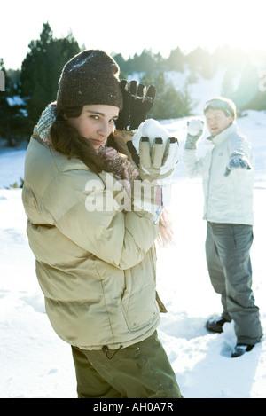 Due giovani amici tenendo premuto fino snowballs, uno guardando sopra la spalla in telecamera Foto Stock