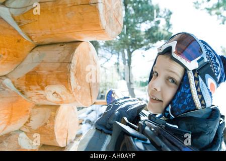 Ragazzo tenendo gli sci in spalla, sorridente sulla spalla in telecamera Foto Stock