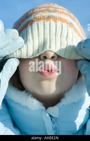 Ragazza tirando knit hat giù sopra gli occhi, raggrinzimento, close-up Foto Stock
