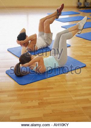 L uomo e la donna facendo esercizio mat Foto Stock