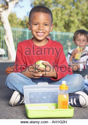 Gli studenti al di fuori della scuola di mangiare Foto Stock