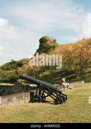 Una femmina di turisti si siede su una parete interna nel Parco Nazionale di Brimstone Hill Fortress St Kitts Foto Stock