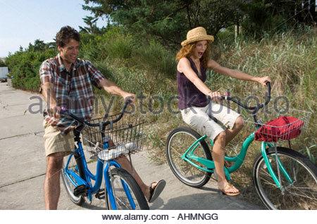 Adulto Giovane equitazione biciclette sul percorso spiaggia Foto Stock