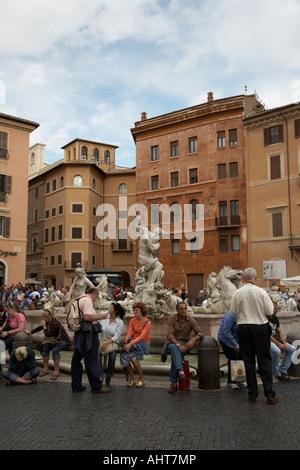I turisti sedersi presso la Fontana del Nettuno in Piazza Navona Roma Lazio Italia