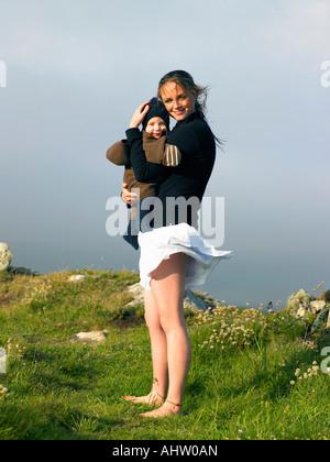 Giovane donna azienda baby con il vento che soffia il suo mantello. Foto Stock
