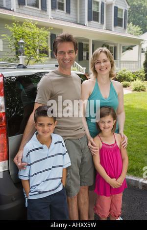 Famiglia in piedi dietro la macchina Foto Stock