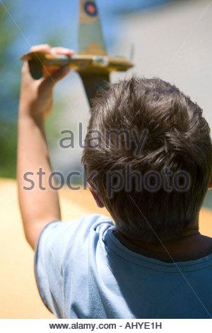Ragazzo 8 10 giocando con il giocattolo aero piano nel giardino estivo vicino la vista posteriore Foto Stock