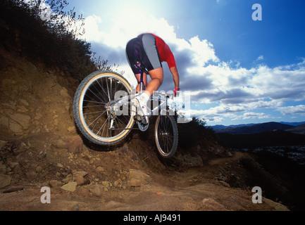 Un mountain biker saltando una discesa su un sentiero singletrack Foto Stock