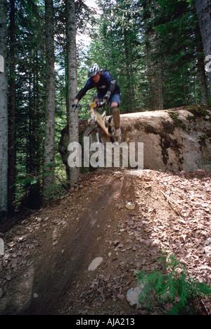 Un mountain biker salta fuori da una roccia in Whistler della Columbia britannica in Canada Foto Stock