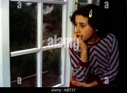 Giovane ragazza a guardare le gocce di pioggia sulla finestra Foto Stock