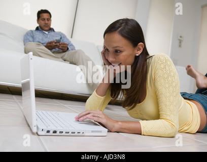 Donna sdraiata sul pavimento con il laptop in soggiorno, vista terra Foto Stock