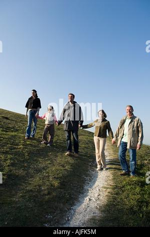 Famiglia camminando mano nella mano sulla collina Foto Stock