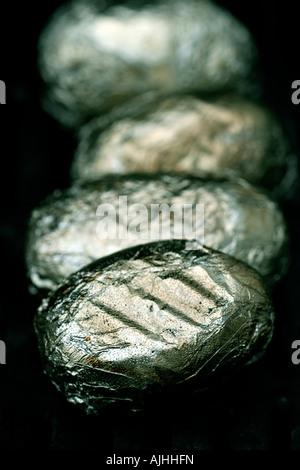 Patate avvolto in alluminio sfrigolante su barbecue Foto Stock