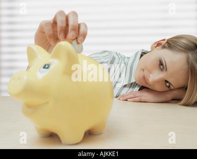 Donna mettendo moneta nel salvadanaio Foto Stock