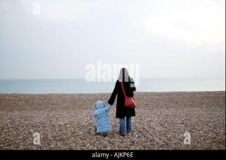 Madre e figlia su una spiaggia in inverno Foto Stock