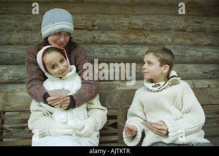 Giovani amici in abbigliamento invernale carte da gioco Foto Stock