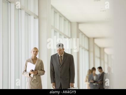 I dirigenti a piedi attraverso il corridoio di edificio per uffici Foto Stock