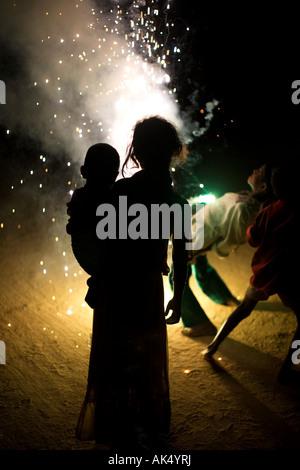 Indian bambini che giocano attorno a fuochi d'artificio di Diwali su un indiano street Foto Stock