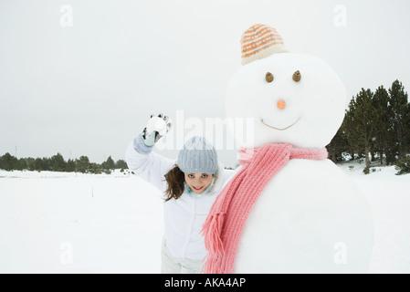Giovane donna in piedi accanto al pupazzo di neve, pronto a lanciare palle di neve in telecamera Foto Stock