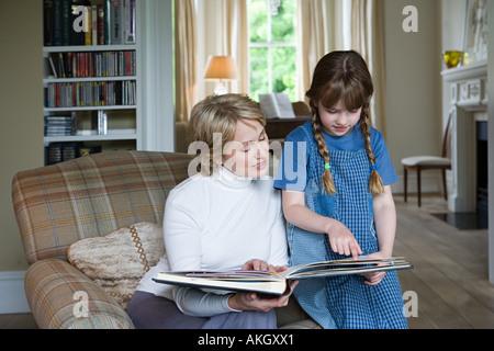 La ragazza e la nonna guardando scrapbook Foto Stock