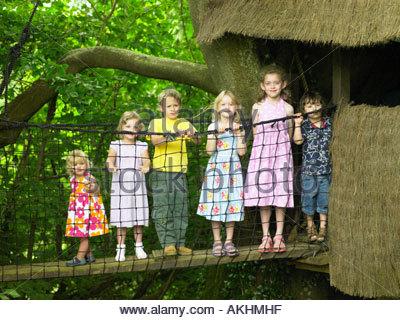 I bambini su un albero di casa bridge Foto Stock