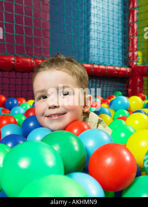 Ragazzo in una piscina di palline Foto Stock