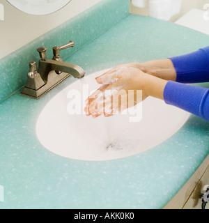 Primo piano di lavaggio delle mani nel lavandino del bagno Foto Stock
