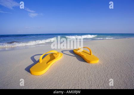 Coppia di giallo flip flop sandals sulla spiaggia vicino waters edge in Playa del Carmen, Messico Foto Stock