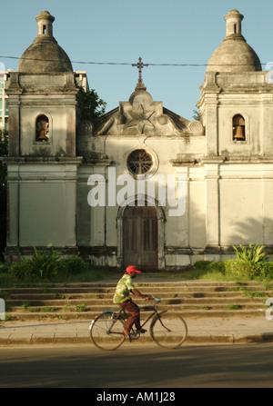 Un uomo di cicli la sua bici passato un abbandonato cattedrale portoghese a Quelimane città. Mozambico, Sud Africa Foto Stock