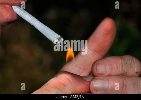 Un uomo di accendere una sigaretta di rollup con la fiamma di un ...