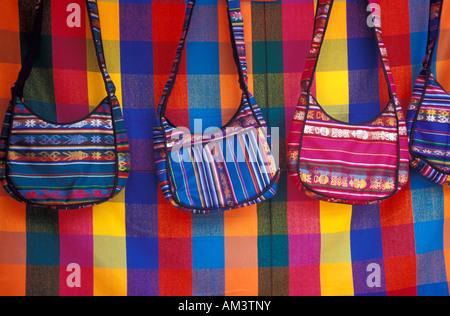 Tessuto borse a tracolla per la vendita al mercato di artigianato in Poncho Plaza, Otavalo, Ecuador Foto Stock