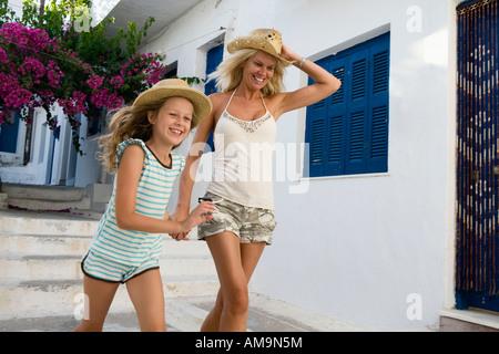 Donna e bambina in esecuzione al di fuori di casa sorridente. Foto Stock