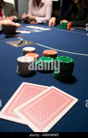 Carte da gioco e pile di fiches sul tavolo del casinò Foto Stock