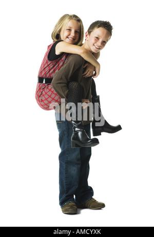Ragazzo dando ragazza piggy back ride sorridente Foto Stock