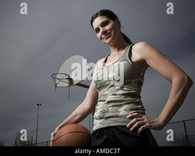 Donna che mantiene la pallacanestro con net in background Foto Stock