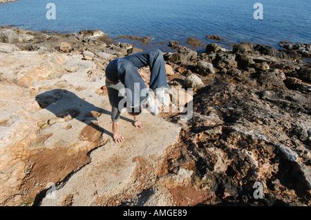 Razza mista giovane donna metà metà asiatica spagnolo esercizio oudoors e facendo un handstand a Ibiza Spagna Foto Stock