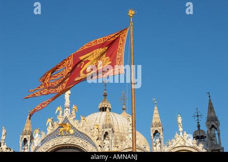 Venezia, Italia bandiera veneziana volando sopra di San Marco la Basilica. Foto Stock