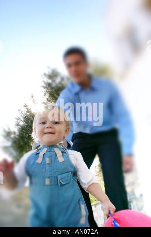 Little Boy giocare ''catch me se è possibile'' di uomo adulto Foto Stock