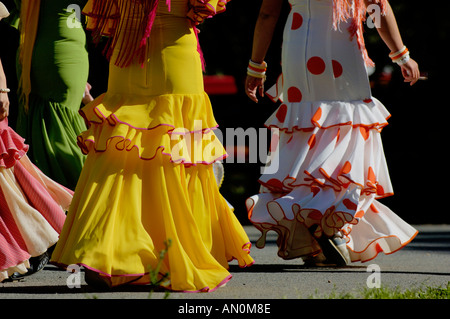 Le donne in abito di flamenco a piedi attraverso il Parco Maria Luisa di Siviglia durante la Fiera di Primavera, Feria de Abri, Siviglia, in Andalusia, Spagna. Foto Stock