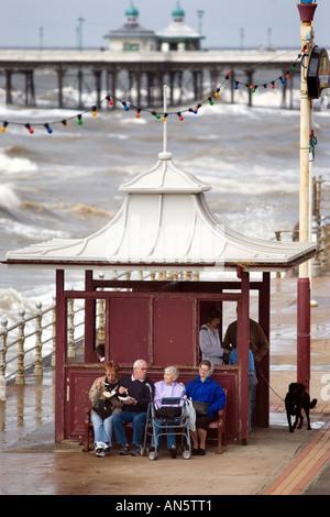 I visitatori a Blackpool Regno Unito sedersi davanti a un rifugio sul lungomare su un Ferragosto Foto Stock