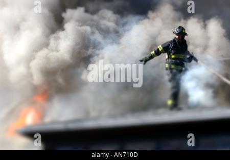 Vigile del fuoco su un tetto a combattere un incendio
