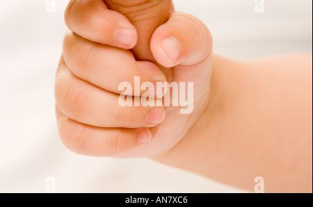 Bambino di 4 mesi tenendo le madri mano aggrapparsi reflex Foto Stock
