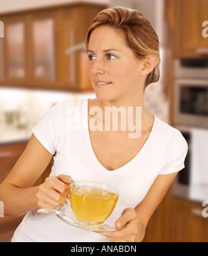 La donna in cucina a bere il tè alle erbe Foto Stock