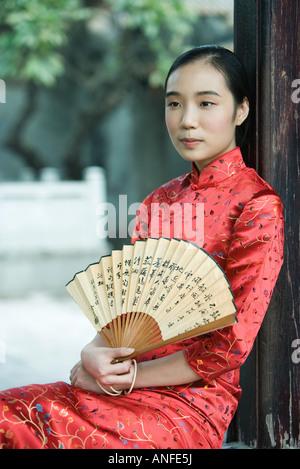 Giovane donna che indossa il cinese tradizionale abbigliamento, mantenendo la ventola, ritratto Foto Stock